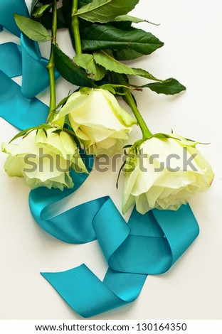 Three white roses with blue ribbon as a gift - stock photo