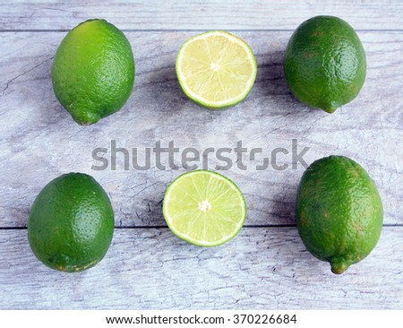 three whole and one half  limes and one line cut in half on a gray wooden background/beautiful limes/ limes - stock photo