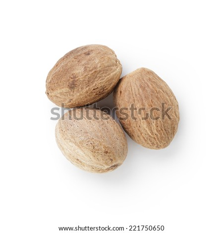 three whole dried nutmegs, isolated on white - stock photo