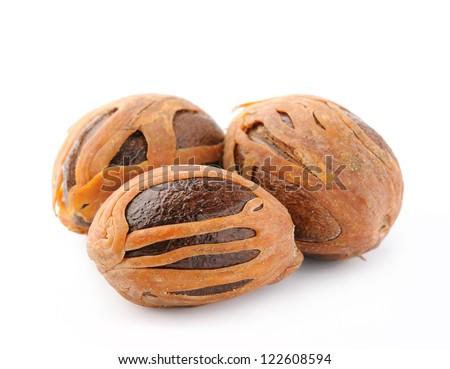 Three whole nutmegs on white background - stock photo