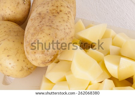 Three Whole Potatoes and Chopped Peeled Pieces on Cutting Board - stock photo