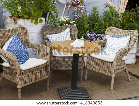 Three wicker chairs and a little table of street cafe.