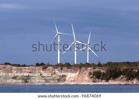 three wind generators of larger wind farm on the coastal cliff at waterfront in Estonia