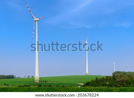 Three wind power generators on the green meadow - stock photo
