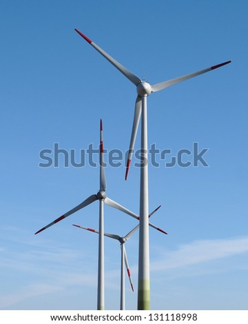 Three wind power turbines on blue sky background - stock photo