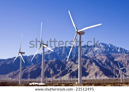 Three wind turbines loom above a field of hundreds such power generators - stock photo