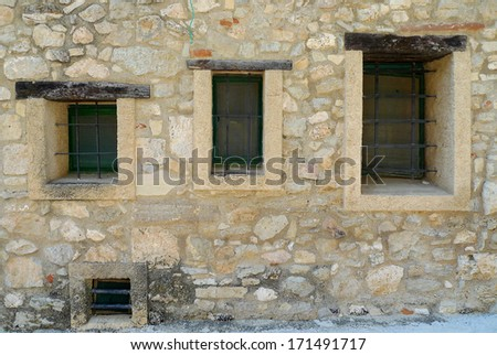 Three windows on a wall of an old house in a village in Spain
