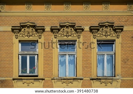 Three windows with flowers in one of them - stock photo