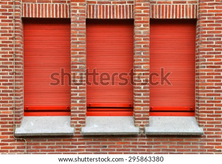 three windows with red roller shutter - stock photo
