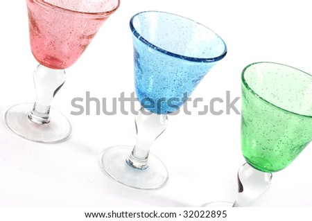 Three wine glasses sit diagonally on a white background