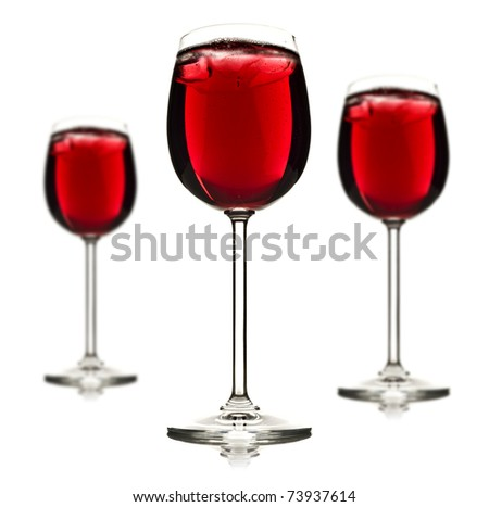 Three wine glasses with red fruit juice and ice on a white background - stock photo