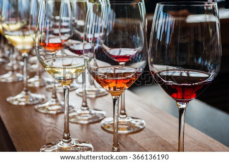 Three wine glasses with white, rose, and red wine samples, on wood counter with other glasses in background. - stock photo