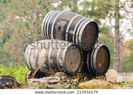 Three wine or whiskey barrels stacked outside on their sides.  - stock photo
