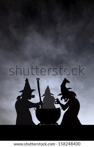Three witches gathering to brew magic potion in a cauldron on Halloween night.  - stock photo