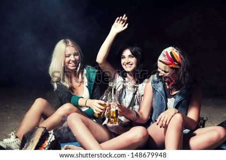 three woman drinks beer on the beach - stock photo