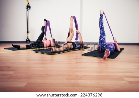 Three women are stretching their legs with resistance bands in the gym - stock photo