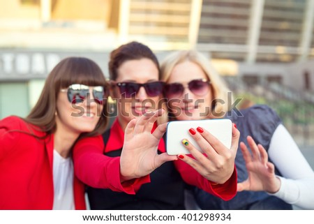Three women currently make selfie portrait of a mobile phone. Group young happy women making selfie and smiling. - stock photo