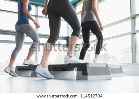 Three women doing aerobics in gym