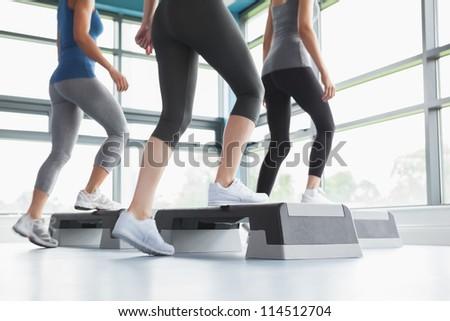 Three women doing aerobics in gym - stock photo