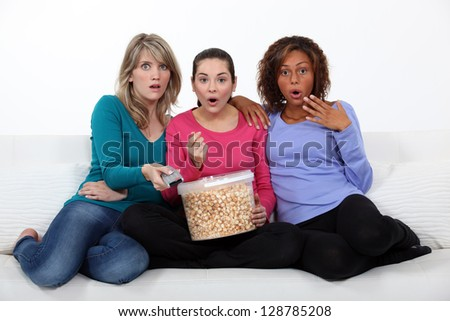 Three women eating popcorn whilst watching film - stock photo