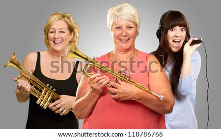 Three Women Enjoying Music On Gray Background - stock photo