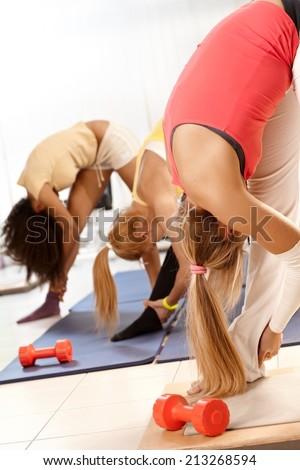 Three women exercising at the gym, bending, hugging leg. - stock photo