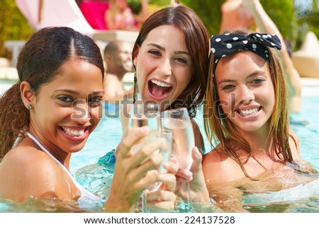 Three Women Having Party In Swimming Pool Drinking Champagne - stock photo