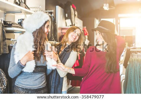 Three women in a clothing store enjoying shopping time. They are trying some hats, looking each other smiling and laughing. Friendship, lifestyle and consumerism concepts.