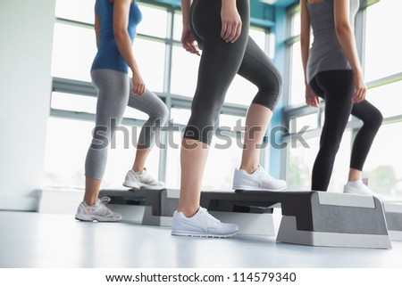 Three women in aerobics class in gym - stock photo