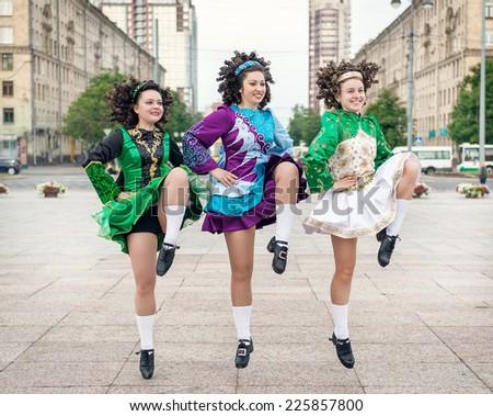 Three women in irish dance dresses dancing outdoor - stock photo