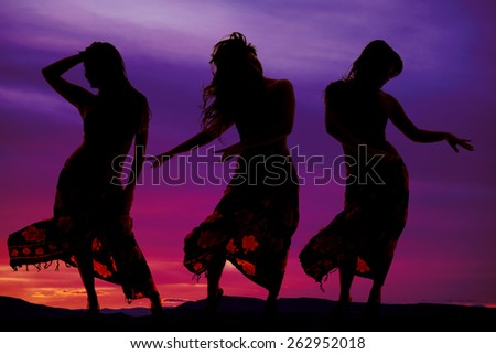 Three women in their sarongs dancing in the outdoors - stock photo