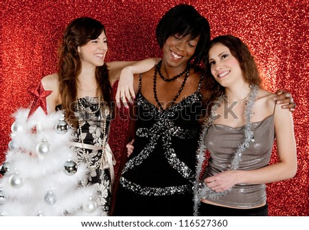 Three women laughing at a christmas party, having fun with a white decorated tree in a red glitter background.