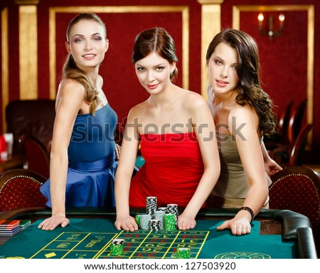 Three women place a bet playing roulette at the casino - stock photo