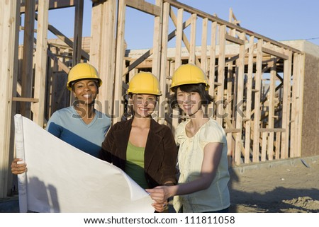 Three women reviewing blueprint at construction site - stock photo