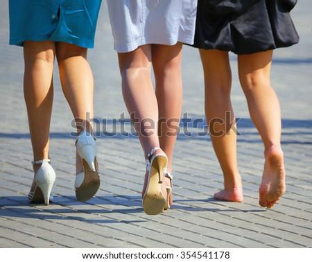 Three women's legs - stock photo
