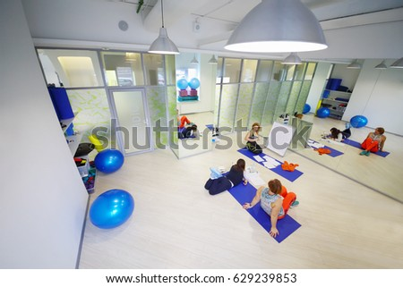 Three women (teacher and two students) are in hall for fitness