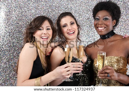 Three women toasting with champagne at a party against a silver glitter background.