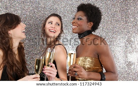 Three women toasting with champagne at a party against a silver glitter background, laughing.