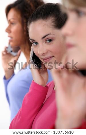Three women using their mobile telephones - stock photo