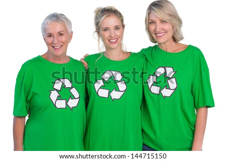 Three women wearing green recycling tshirts smiling at camera on white background - stock photo
