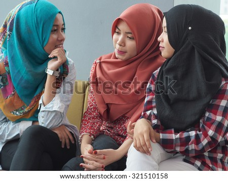 Three women wearing hijab are in a discussion. - stock photo