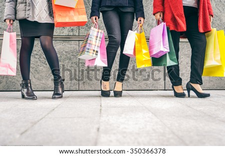 Three women with a lot of shopping bags - stock photo