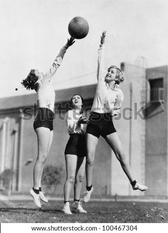 Three women with basketball in the air - stock photo