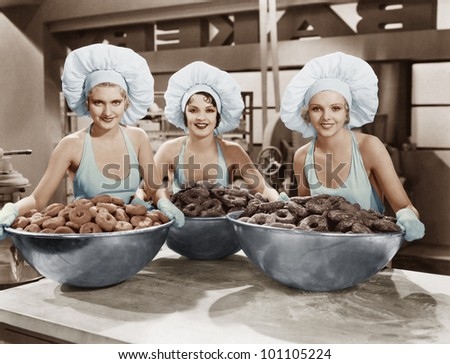 Three women with huge bowls of donuts - stock photo