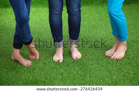 Three women with naked feet standing in grass - stock photo