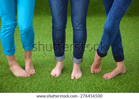 Three women with naked feet standing in grass