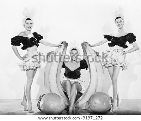 Three women with oversized fruits