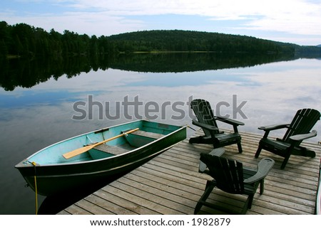 Three wooden adirondack chairs on a boat dock on a beautiful lake in the evening - stock photo