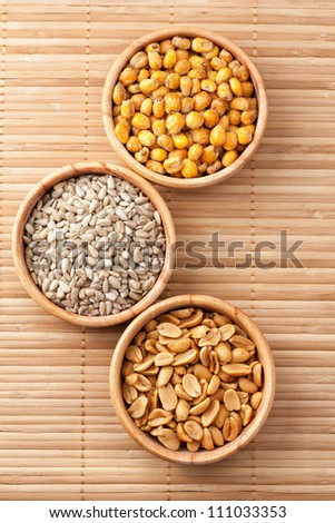 Three wooden bowls with roasted salted corn, sunflower seed and peanuts