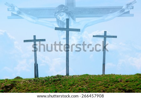 Three wooden crosses on a grassy hill with Jesus on the cross in the clouds in the background. - stock photo